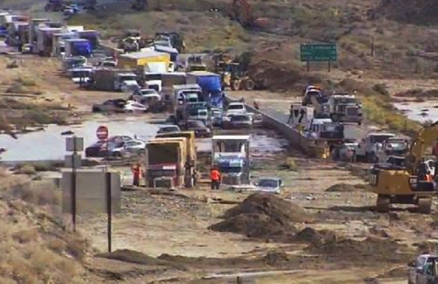 This image made from video provided by KABC-TV shows some of hundreds of big rigs and cars stranded on State Highway 58 near Mojave, Calif., Friday, Oct. 16, 2015, after torrential rains Thursday caused mudslides that carried away vehicles and closed roads about 70 miles north of Los Angeles. Rescuers threw ladders and tarps across mud up to 6 feet deep to help hundreds of trapped people from cars that got caught in a roiling river of mud along a major Southern California trucking route, a California Highway Patrol official said Friday in what he and other witnesses described as a chaotic scene. Amazingly, officials said, no deaths or injuries were reported. (KABC-TV via AP) MANDATORY CREDIT NO SALES TV OUT